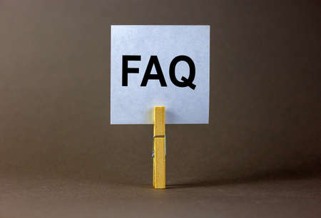 FAQ, frequently asked questions symbol. White paper on wooden clothespin. Words 'FAQ, frequently asked questions'. Beautiful gray background. Business and FAQ concept, copy space.