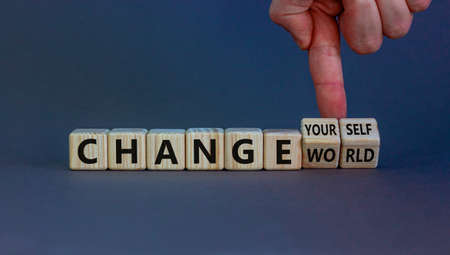Change world or yourself symbol. Businessman turns wooden cubes and changes words 'change world' to 'change yourself'. Beautiful gray background, copy space. Business and change yourself concept. Banque d'images