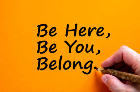 Belonging symbol. Hand writing 'be here, be you, belong', isolated on orange background. Business, belonging and better inclusion, belong here concept. Copy space.