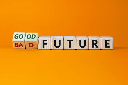 Good or bad future symbol. Turned wooden cubes and changed words 'bad future' to 'good future'. Beautiful orange background, copy space. Business and bad or good future concept. Imagens