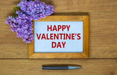 February 14 valentines day symbol. Wooden frame with words 'Happy valentines day'. Lilac branch and metalic pen. Beautiful wooden background, copy space. Happy Valentines day concept.