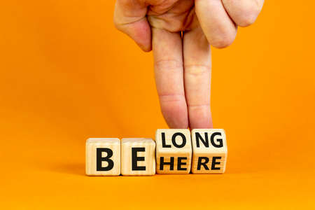 Be here belong symbol. Businessman hand turns cubes and changes words 'be here' to 'belong'. Beautiful orange background. Business, belonging and be here belong concept. Copy space.
