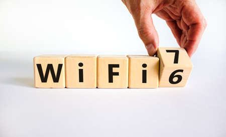WiFi 6 or 7 symbol. Businessman turns a wooden cube and changes the words WiFi 6 to WiFi 7. Beautiful white background, copy space. Business, technology and WiFi 6 to WiFi 7 concept. Stock Photo
