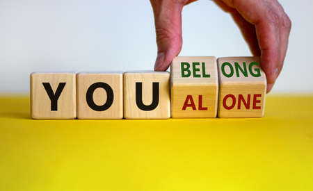 You alone or belong symbol. Businessman turns cubes and changes words you alone to you belong. Beautiful white background. Business, psychology and you alone or belong concept. Copy space.