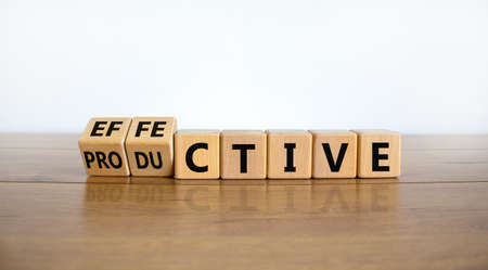 Effective and productive symbol. Turned wooden cubes, changed the word 'productive' to 'effective'. Beautiful wooden table, white background, copy space. Business, effective and productive concept.