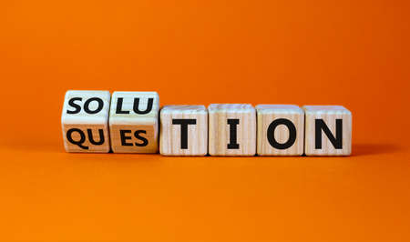 Question and solution symbol. Turned wooden cubes and changed the word 'question' to 'solution'. Beautiful orange table, orange background, copy space. Business, question and solution concept.