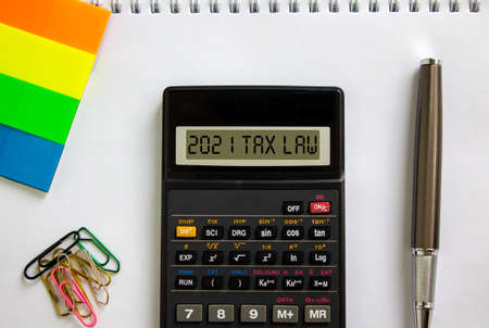 2021 tax law symbol. Calculator with words '2021 tax law', white note, colored paper, paper clips, pen. Beautiful white background. Business and 2021 tax law concept.