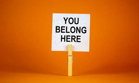 You belong here symbol. Wooden clothespin with white paper. Words 'you belong here'. Beautiful orange background. Business and you belong here support concept, copy space.