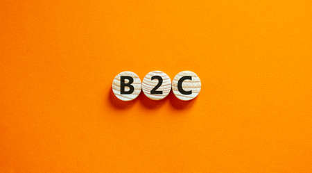B2C, business to customer symbol. Wooden circles with word 'B2C, business to customer'. Beautiful orange background. B2C, business to customer concept. Copy space.