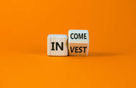 Invest or income symbol. Turned a wooden cube and changed the word 'invest' to 'income'. Beautiful orange background, copy space. Business and invest or income concept.