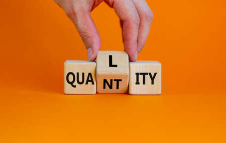 Quality over quantity symbol. Businessman turns cubes and changes the word 'quantity' to 'quality'. Beautiful orange table, orange background, copy space. Business and quality over quantity concept.