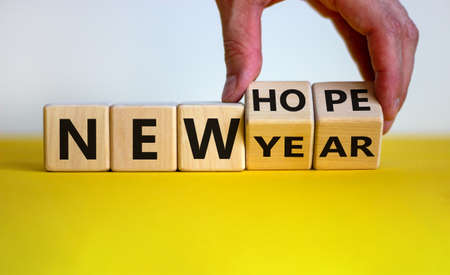 New year and hope symbol. Businessman turns cubes and changes the words 'new year' to 'new hope'. Beautiful white and yellow background. Copy space. Business and new year - new hope concept.