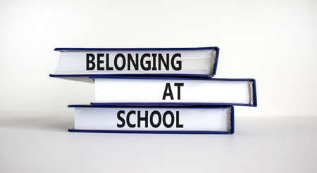 Belonging at school symbol. Books with words 'Belonging at school' on beautiful white background. Business, belonging at school concept. Copy space.