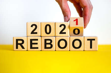 Symbol of 2021 reboot. Businessman turns a wooden cube and changes words 'reboot 2020' to 'reboot 2021'. Beautiful yellow and white background, copy space. Business and 2021 new year reboot concept.