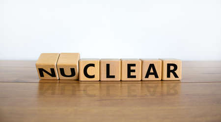 Nuclear or clear symbol. Turned wooden cubes and changed the word 'nuclear' to 'clear'. Beautiful wooden table, white background. Nuclear or clear and business concept. Copy space.