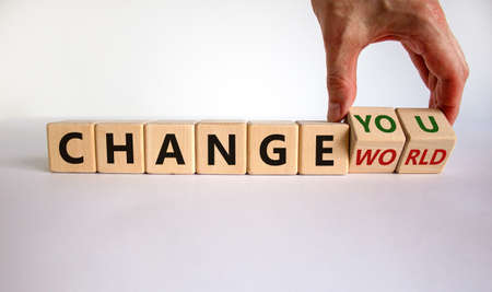 Change world or you symbol. Businessman turns wooden cubes and changes words 'change world' to 'change you'. Beautiful white background, copy space. Business and change yourself concept.