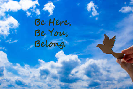 Belong symbol. Man hand holding wooden bird on cloud blue sky background. Words 'be here, be you, belong'. Business, belonging and inclusion concept. Copy space.