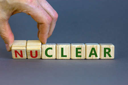 Nuclear or clear symbol. Businessman turns a cube and changes the word 'nuclear' to 'clear'. Beautiful gray background. Nuclear or clear and business concept. Copy space.