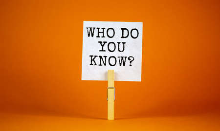Who do you know symbol. White paper with words 'who do you know', clip on wood clothespin. Beautiful orange background. Business, support and who do you know concept, copy space.