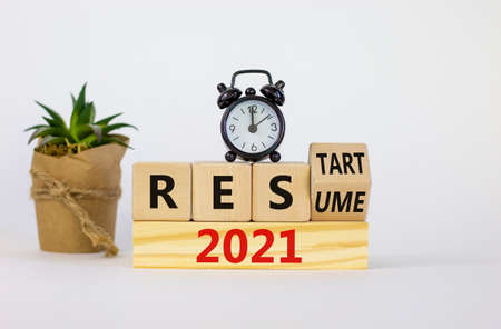 2021 resume and restart symbol. Turned a cube and changed words '2021 resume' to '2021 restart'. Alarm clock. Beautiful white background. Business and 2021 resume - restart concept. Copy space.