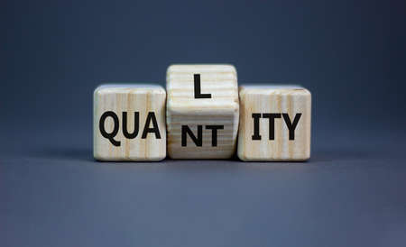 Quality over quantity symbol. Turned cubes and changed the word 'quantity' to 'quality'. Beautiful gray table, gray background, copy space. Business and quality over quantity concept. Stock Photo