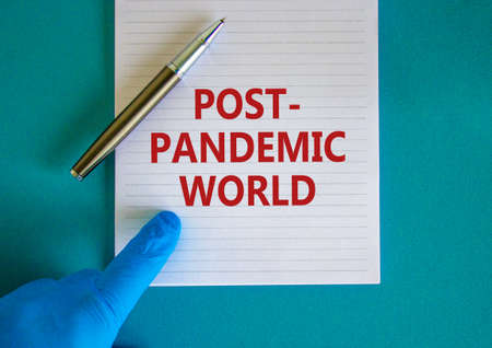Post-pandemic world symbol. Hand in blue glove with white card. Concept words 'Post-pandemic world'. Metalic pen. Medical and COVID-19 pandemic post-pandemic world concept. Copy space.