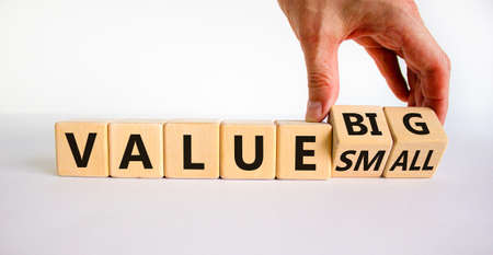 Small or big value symbol. Businessman turns wooden cubes and changes words 'value small' to 'value big'. Beautiful white background, copy space. Business and small or big value concept.