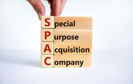 SPAC, special purpose acquisition company symbol. Businessman holds cubes with words 'SPAC' on beautiful white background, copy space. Business and SPAC, special purpose acquisition company concept. Stock Photo