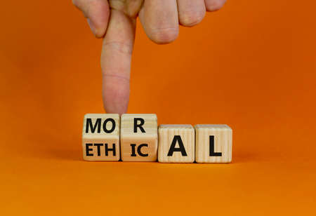 Ethical or moral symbol. Businessman turns wooden cubes and changes the word 'moral' to 'ethical' on a beautiful orange table, orange background. Business and ethical or moral concept. Copy space.