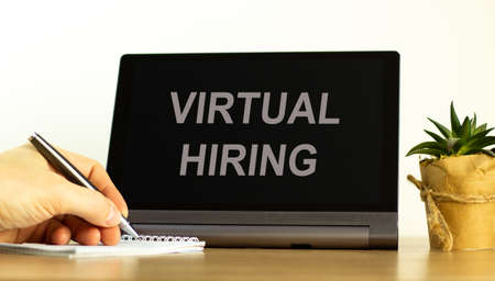Virtual hiring symbol. Tablet with words 'Virtual hiring'. Businessman hand, pen, house plant. Copy space. Virtual hiring concept. Imagens