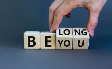 Be you, belong symbol. Businessman hand turns cubes and changes words 'be you' to 'belong'. Beautiful gray background. Business, belonging and be you, belong concept. Copy space.