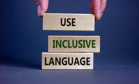 Use inclusive language symbol. Wooden blocks with words 'Use inclusive language'. Beautiful gray background, businessman hand. Business and use inclusive language concept. Copy space.
