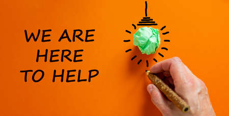 Support symbol. Businessman writing 'we are here to help', isolated on beautiful orange background. Light bulb icon. Business and support concept. Copy space.