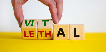 Vital vs lethal symbol. Businessman turns wooden cubes and changes the word 'lethal' to 'vital'. Beautiful yellow table, white background, copy space. Business and vital vs lethal concept.
