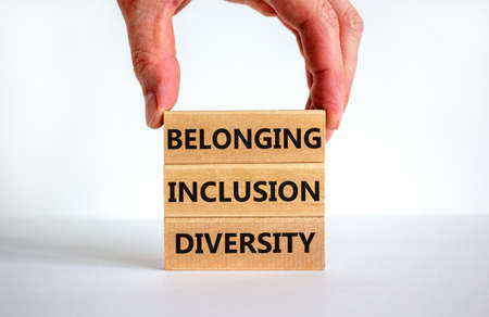 Diversity, inclusion and belonging symbol. Wooden blocks with words 'diversity, inclusion, belonging' on beautiful white background. Male hand. Diversity, business, inclusion and belonging concept. Stock fotó