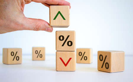 Interest rates symbol. Wooden cubes, businessman changed the direction of an arrow symbolizing that the interest rates are going down or up. Beautiful white background. Business concept. Copy space. Stock Photo