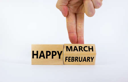 Symbol for the change from February to March. Businessman turns wooden cubes and changes words 'Happy February' to 'Happy March'. Beautiful white background, copy space. Happy March concept.