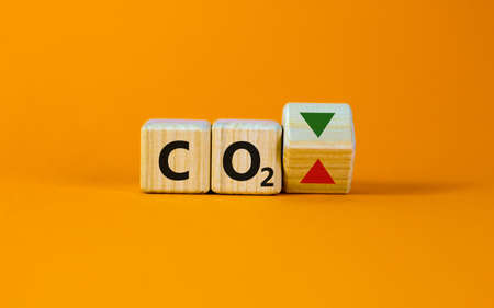 CO2 changes symbol. Concept words 'CO2' on cubes on a beautiful orange table, orange background. Business and CO2 changes concept. Copy space.