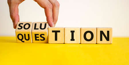 Question and solution symbol. Businessman turns wooden cubes and changes the word 'question' to 'solution'. Beautiful yellow table, white background, copy space. Business, question and solution concept.
