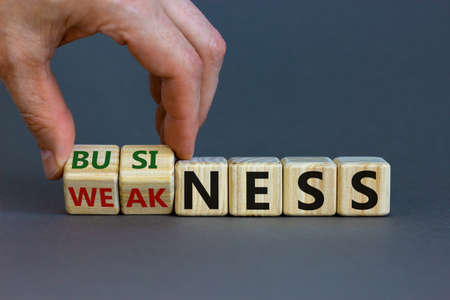 Business or weakness symbol. Businessman hand turns wooden cubes and changes the word 'weakness' to 'business'. Beautiful gray background, copy space. Business or weakness concept.