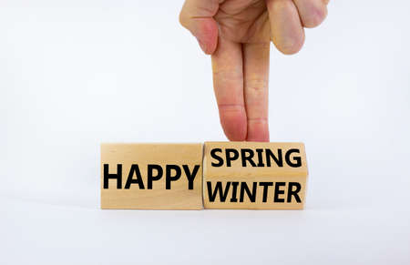 Symbol for the change from Winter to Spring. Businessman turns wooden cubes and changes words 'Happy Winter' to 'Happy Spring'. Beautiful white background, copy space. Happy Spring concept.