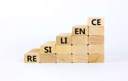 Resilience symbol. Wooden blocks with word 'resilience' stacking as step stair on beautiful white background, copy space. Business and resilience concept success process.