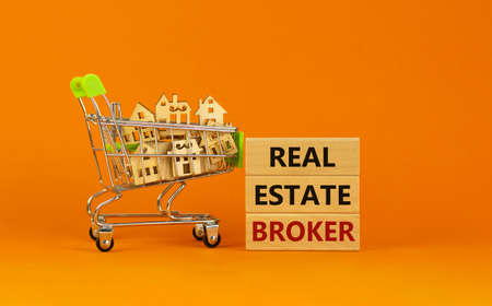 Real estate broker symbol. Wooden blocks with words 'Real estate broker' on beautiful orange background. Shopping cart with miniature wooden houses. Business, Real estate broker concept. Copy space. 版權商用圖片
