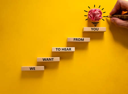 Business concept growth success process. Wood blocks stacking as step stair on yellow background, copy space. Businessman hand. Words 'we want to hear from you'. Conceptual image of motivation.