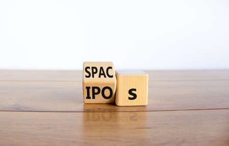 SPACs vs IPOs symbol. Cubes with words 'SPACs, special purpose acquisition companies' and 'IPOs, initial public offering' on beautiful white background, copy space. Business and SPACs vs IPOs concept. Stock Photo