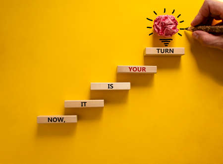 Business concept growth success process. Wood blocks stacking as step stair on yellow background, copy space. Businessman hand. Words 'now, it is your turn'. Conceptual image of motivation.