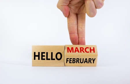 Symbol for the change from February to March. Businessman turns wooden cubes and changes words 'Hello February' to 'Hello March'. Beautiful white background, copy space. Hello March concept.