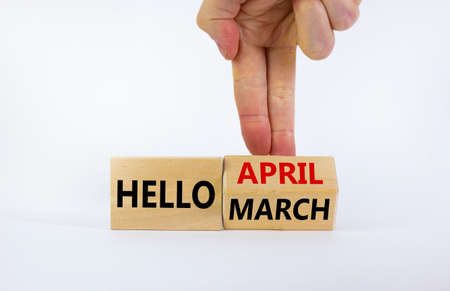 Symbol for the change from March to April. Businessman turns wooden cubes and changes words 'Hello March' to 'Hello April'. Beautiful white background, copy space. Hello April concept.