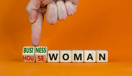 Housewoman or businesswoman symbol. Businessman turns cubes and changes the word housewoman to businesswoman. Beautiful orange background, copy space. Gender equality, businesswoman concept.