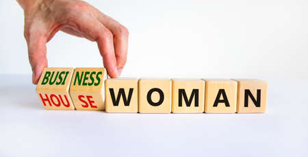 Housewoman or businesswoman symbol. Businessman turns cubes and changes the word housewoman to businesswoman. Beautiful white background, copy space. Gender equality, businesswoman concept.